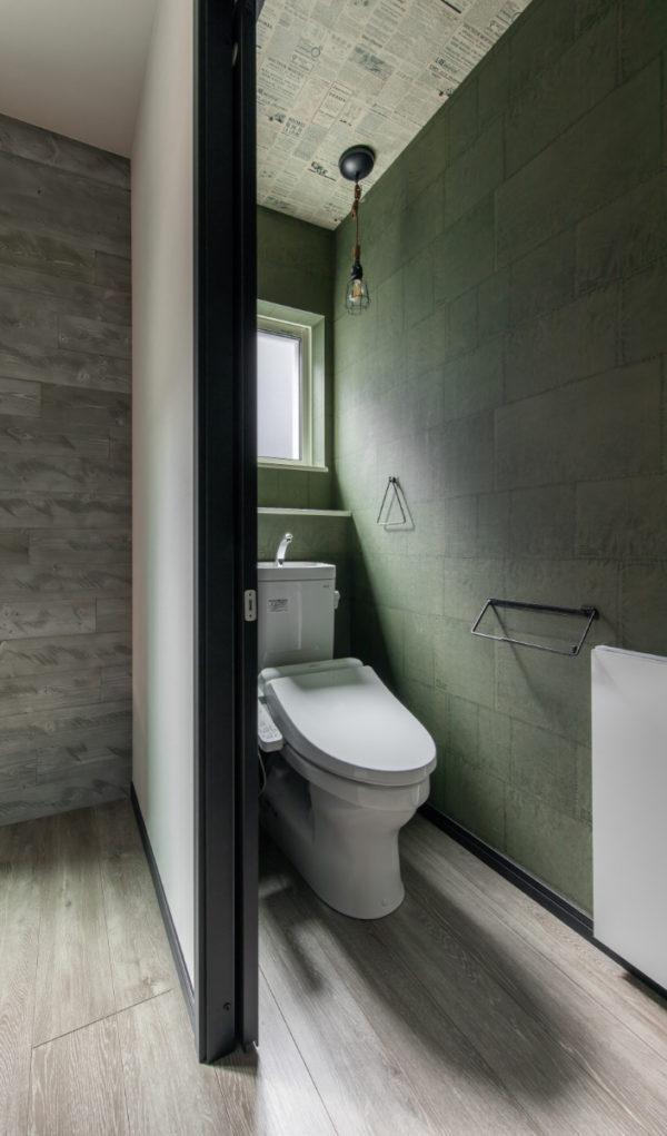 落ち着いたグリーンのクロスに壁埋め込み収納のあるトイレ(2F)